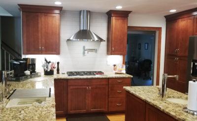 Stainless steel range hood, pot filler, cherry cabinets, white subway tile back